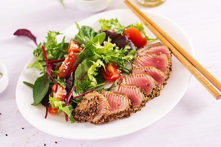 Japanese traditional salad with pieces of medium-rare grilled Ahi tuna and sesame with fresh vegetable salad on a plate. Authentic Japanese food. Stok Fotoğraf