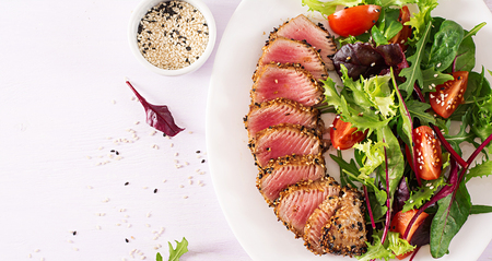 Japanese traditional salad with pieces of medium-rare grilled Ahi tuna and sesame with fresh vegetable salad on a plate. Authentic Japanese food. Top view. Copy space. Reklamní fotografie