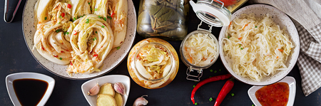Fermented food. Vegetarian food concept. Cabbage kimchi, tomatoes marinated, sauerkraut sour glass jars over rustic kitchen table. Canned food concept. Top view. Banner. Flat lay