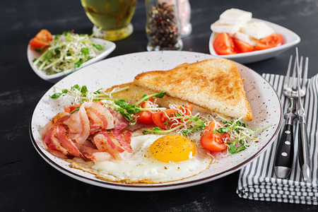 English breakfast - toast, egg, bacon and tomatoes and microgreens salad. 免版税图像