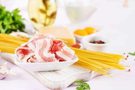 Bacon. Ingredients for cooking Carbonara pasta, spaghetti, egg, peppers, salt and hard parmesan cheese. Italian cuisine.