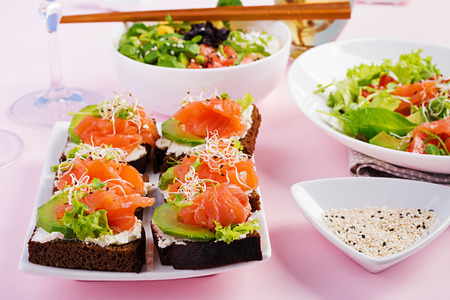 Healthy breakfast. Buddha bowl with rice, mango, avocado and salmon and fresh salad with tomatoes, avocado, arugula, seeds, salmon and salmon sandwich with avocado, creame cheese and microgreen. Healthy food concept. Imagens