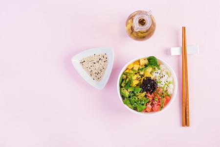Buddha Bowl mit Reis, Mango, Avocado und Lachs. Gesundes Lebensmittelkonzept. Ansicht von oben. Flach legen