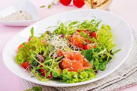 Diet menu. Healthy salad of fresh vegetables - tomatoes, avocado, arugula, seeds and salmon on a bowl. Vegan food.