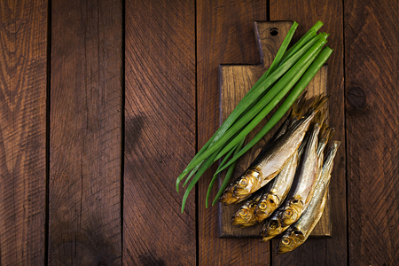 Smoked sprat and green onion  on a cutting board on a wooden background. Smoked fish. Top view
