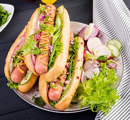 Hot dog with  sausage, cucumber, radish and lettuce on dark wooden background. Summer hotdog.