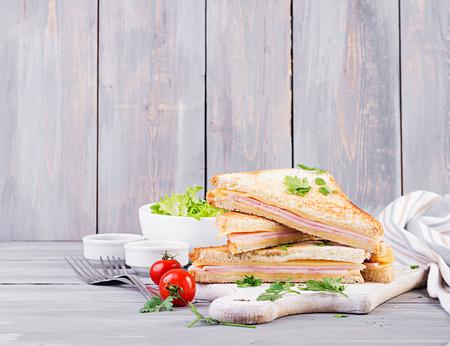 Panini club sándwich con jamón, queso y ensalada. Desayuno sabroso
