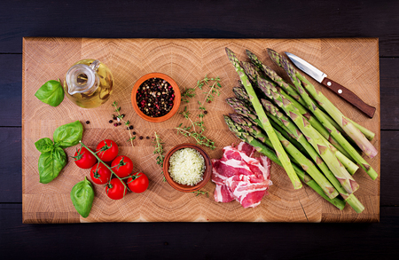 Fresh green asparagus and bacon on a rustic wooden table with copy space. Top view