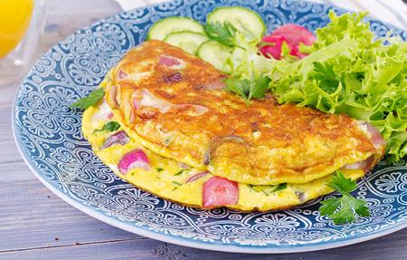 Petit-déjeuner. Omelette aux radis, oignon rouge et salade fraîche sur plaque bleue. Frittata - omelette italienne.