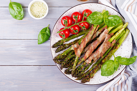 Grilled green asparagus wrapped with bacon on wooden table. Top view Standard-Bild