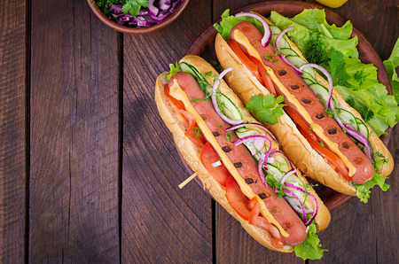 Hot dog with sausage, cucumber, tomato and lettuce on dark wooden background. Summer hotdog. Top view