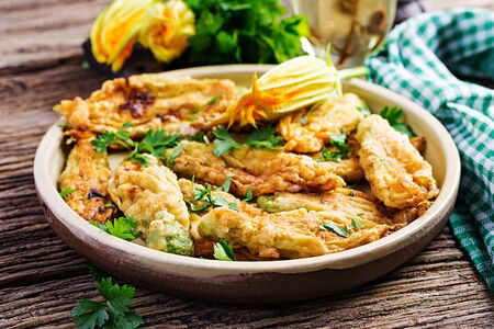 Fried zucchini flowers stuffed with ricotta and green herbs. Vegan food. Italian cuisine.