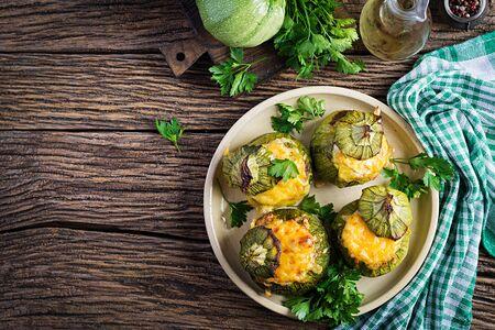 Calabacín relleno de carne picada, queso y hierbas verdes. Al horno en horno. Vista superior Foto de archivo