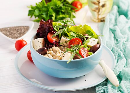 Vegan salad. Breakfast bowl with oatmeal, tomatoes, cheese, lettuce,  and olives. Healthy food. Vegetarian buddha bowl. Reklamní fotografie