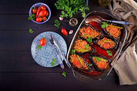 Karniyarik - comida tradicional turca de berenjena y berenjena. Berenjenas rellenas de carne molida y verduras al horno con salsa de tomate. Cocina turca. Vista superior. Copia espacio