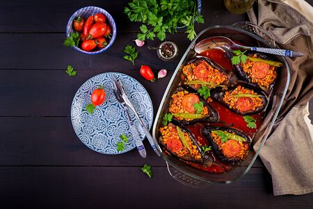 Karniyarik - turkish traditional aubergine eggplant meal. Stuffed eggplants with ground beef and vegetables baked with tomato sauce. Turkish cuisine. Top view. Copy space