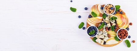 Cheese platter with assorted cheeses, blueberry, apples, nuts on white table. Italian cheese platter and fruit. Banner. Top view, overhead Stock Photo