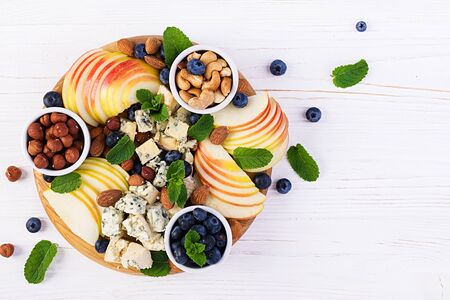 Cheese platter with assorted cheeses, blueberry, apples, nuts on white table. Italian cheese  platter and fruit. Top view, overhead Foto de archivo