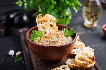 Baba ghanoush vegan hummus from eggplant with seasoning, parsley and toasts. Baba ganoush. Middle Eastern cuisine.