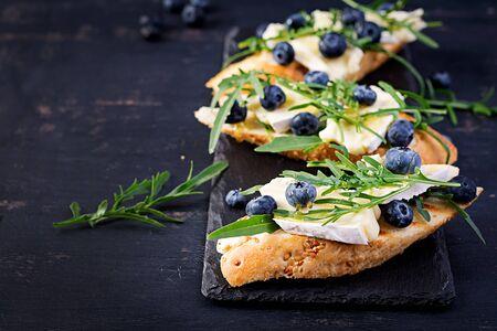 Bruschetta. Toast crostini with fresh berries blueberry and honey, brie cheese, arugula. Italian cuisine