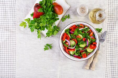 Tomato and cucumber salad with red onion, paprika, black pepper and parsley. Vegan food. Diet menu. Top view. Flat lay