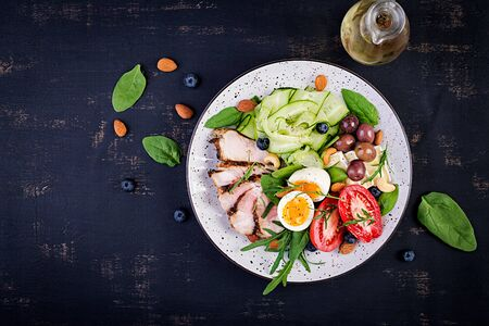 Ketogenic diet. Keto brunch. Boiled egg, pork steak and olives, cucumber, spinach, brie cheese, nuts and tomato. Top view