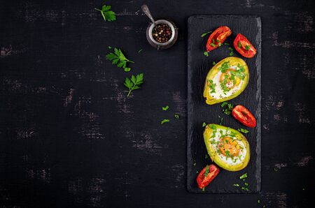 Avocado baked with egg and fresh salad. Vegetarian dish. Top view, overhead.  Ketogenic diet. Keto food 版權商用圖片