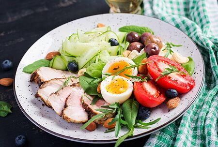 Ketogenic diet. Keto brunch. Boiled egg, pork steak and olives, cucumber, spinach, brie cheese, nuts and tomato.