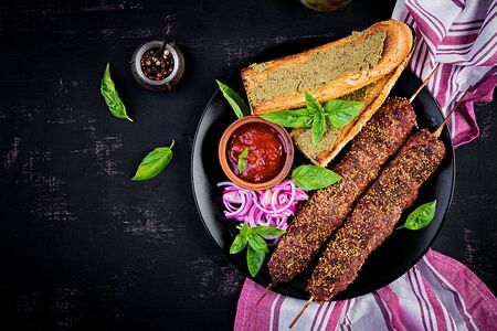 Kebab adana,  lamb and beef and toasts with pesto sauce. Top view