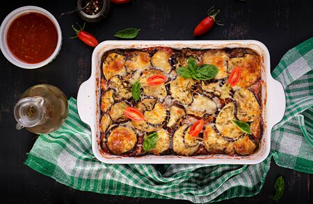 Baked eggplant with cheese on a dark wooden table. Parmigiana melanzane. Top view. Italian cuisine. Copy space
