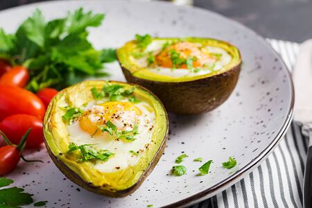 Avocado baked with egg and fresh salad. Vegetarian dish. Ketogenic diet. Keto food