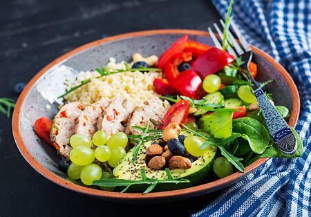 Buddha bowl dish with meatloaf, bulgur, avocado, sweet pepper, tomato, cucumber, berries and nuts. Detox and healthy superfoods bowl concept.