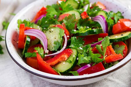 Tomato and cucumber salad with red onion, paprika, black pepper and parsley. Vegan food. Diet menu.