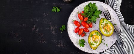 Avocado baked with egg and fresh salad. Vegetarian dish. Top view, overhead.  Ketogenic diet. Banner. Keto food 版權商用圖片