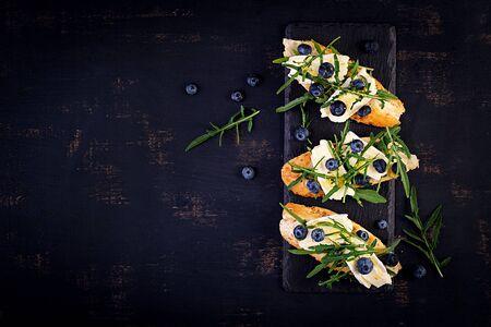 Bruschetta. Toast crostini with fresh berries blueberry and honey, brie cheese, arugula. Top view, copy space. 版權商用圖片