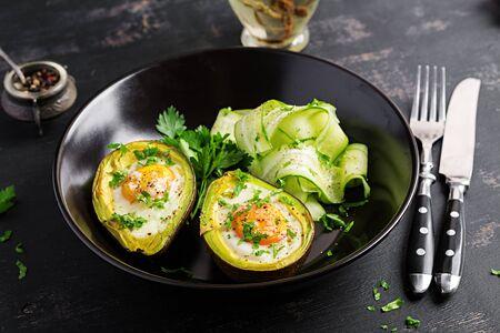 Avocado baked with egg and fresh salad. Vegetarian dish.  Ketogenic diet. Keto food 版權商用圖片