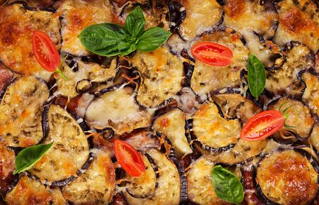 Baked eggplant with cheese on a dark wooden table. Parmigiana melanzane. Top view. Italian cuisine. 版權商用圖片