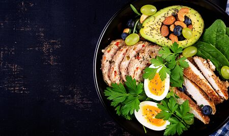Ketogenic diet. Buddha bowl dish with meatloaf, chicken meat, avocado, berries and nuts. Detox and healthy concept. Keto food. Overhead, top view, flat lay
