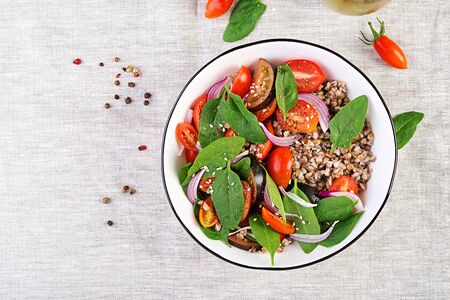Buckwheat salad with cherry tomatoes, red onion and fresh spinach. Vegan food. Diet menu. Top view. Flat lay