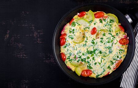 Omelette with tomatoes, zucchini and red onion on dark table.  Frittata - italian omelet. Top view
