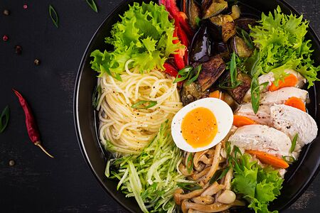 Japanese ramen soup with chicken, egg, shimeji mushrooms and eggplants on dark wooden background. Chanko nabe, sumo soup. Top view Archivio Fotografico - 130410195