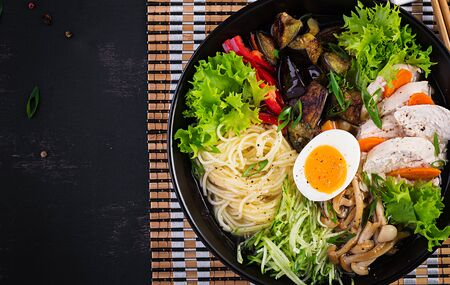 Japanese ramen soup with chicken, egg, shimeji mushrooms and eggplants on dark wooden background. Chanko nabe, sumo soup. Top view Archivio Fotografico