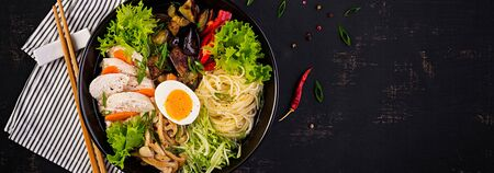 Japanese ramen soup with chicken, egg, shimeji mushrooms and eggplants on dark wooden background. Chanko nabe, sumo soup. Banner. Top view