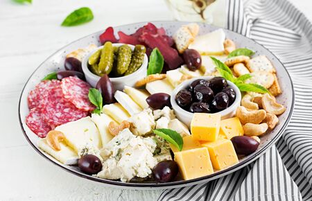 Antipasto platter with basturma, salami, blue cheese, nuts, pickles and olives on a white wooden background. Stock Photo