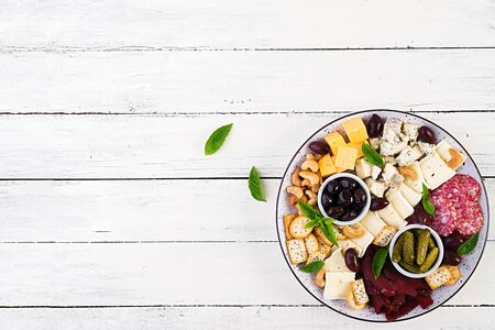 Antipasto platter with basturma, salami, blue cheese, nuts, pickles and olives on a white wooden background. Top view, overhead