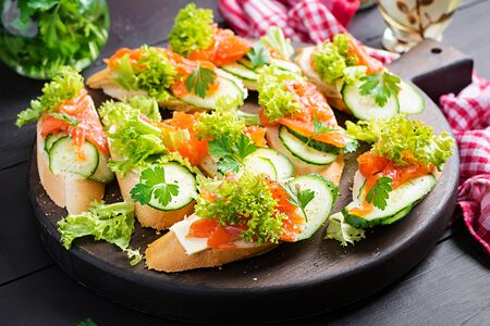 Tapas.  Salted Salmon, butter and cucumber toast sandwiches on wooden board.