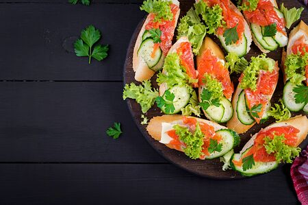 Tapas.  Salted Salmon, butter and cucumber toast sandwiches on wooden board. Top view
