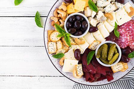 Półmisek antipasto z basturmą, salami, serem pleśniowym, orzechami, piklami i oliwkami na białym drewnianym tle. Widok z góry, nad głową Zdjęcie Seryjne