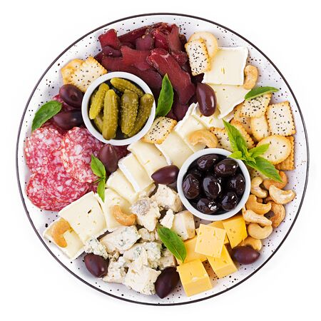 Antipasto platter with basturma, salami, blue cheese, nuts, pickles and olives on a isolated white  background. Top view, overhead