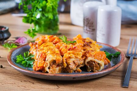 Meat cannelloni pumpkin-tomato sauce on plate.